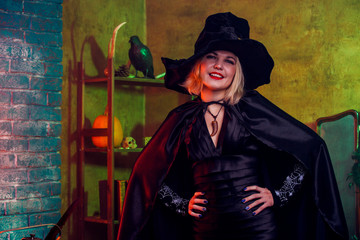 Photo of smiling witch in black hat, dress on background of rack with pumpkin and crow