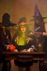 Photo of three witches boiling potion in cauldron