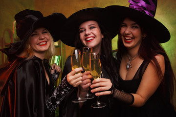 Portrait of three happy witches with glass of champagne