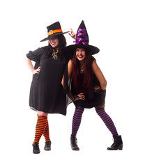 Full-length portrait of two cheerful witches wearing hats and striped socks