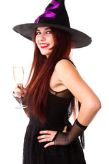 Photo of laughing witch in black hat looking at camera, with glass of champagne
