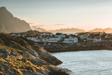 Sunrise and Sunset at Henningsvaer, fishing village located on several small islands in the Lofoten archipelago, Norway over a blue sky with clouds.