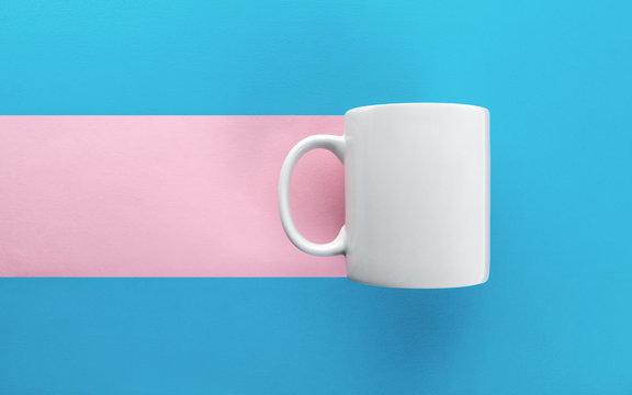 White mug on blue and pink background