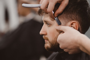 Barbershop Man in barber chair, hairdresser styling his hair razor
