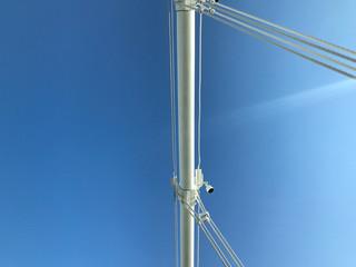 detail of white suspension bridge cables against blue sky