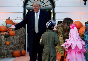 U.S. President Donald Trump and U.S. first lady Melania Trump hand out Halloween candy to trick or treaters at the White House in Washington
