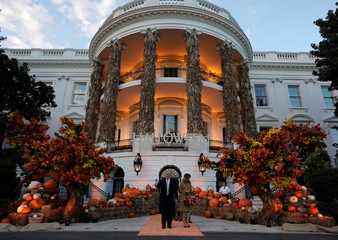 U.S. President Donald Trump and U.S. first lady Melania Trump hand out Halloween candy to trick or-treaters at the White House in Washington