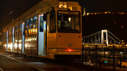 BUDAPEST, HUNGARY - October 26, 2018 Night view of the tram on the background of the Chain Bridge in Budapest, Hungary. Selective focus. Traveling to Hungary