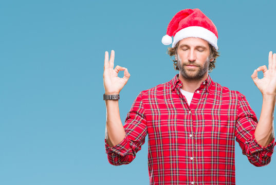 Handsome hispanic man model wearing santa claus christmas over isolated background relax and smiling with eyes closed doing meditation gesture with fingers. Yoga concept.