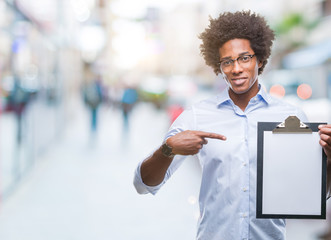 Afro american man holding clipboard over isolated background very happy pointing with hand and finger