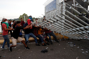 A group of men part of a caravan of thousands of migrants from Central America en route to the U.S, pull down the border gate with the intention to carry on their journey, in Tecun Uman