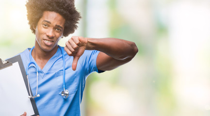 Afro american surgeon doctor holding clipboard man over isolated background with angry face, negative sign showing dislike with thumbs down, rejection concept