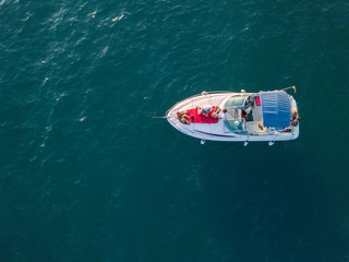 Aerial view of the small yachts floating in the sea by the coast with people on it.