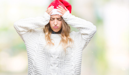 Beautiful young blonde woman wearing christmas hat over isolated background suffering from headache desperate and stressed because pain and migraine. Hands on head.