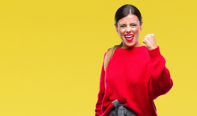 Young beautiful business woman wearing winter sweater over isolated background angry and mad raising fist frustrated and furious while shouting with anger. Rage and aggressive concept.