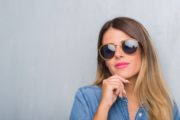 Young adult woman over grunge grey wall wearing retro sunglasses with hand on chin thinking about question, pensive expression. Smiling with thoughtful face. Doubt concept.