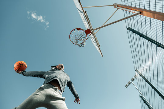 Winning throw. Low angle of a basketball player jumping while doing the winning throw