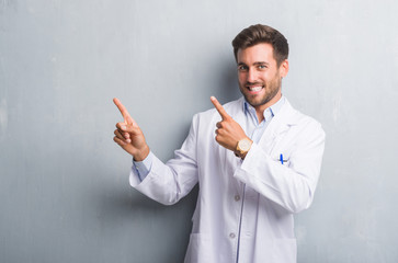 Handsome young professional man over grey grunge wall wearing white coat smiling and looking at the camera pointing with two hands and fingers to the side.