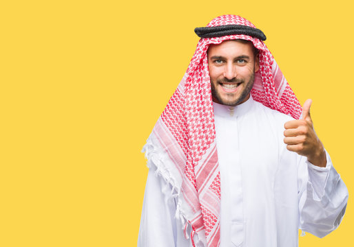 Young handsome man wearing keffiyeh over isolated background doing happy thumbs up gesture with hand. Approving expression looking at the camera with showing success.