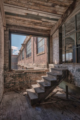 HDR image of the abandoned (now demolished) Scranton Lace Factory in Scranton, Pennsylvania.  Image shows the brick exterior and interior wooden stairs.