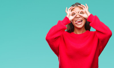 Young beautiful arab woman wearing winter sweater over isolated background doing ok gesture like binoculars sticking tongue out, eyes looking through fingers. Crazy expression.