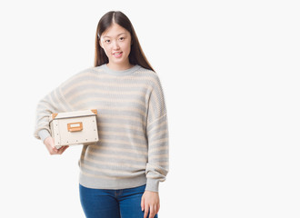Young Chinese woman over isolated background holding a box with a happy face standing and smiling with a confident smile showing teeth
