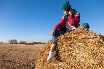 Fashion lifestyle portrait of young trendy woman dressed in pink coat, pink knitted hat  posing, laughing and smiling on a haystack around blue sky.  portrait of joyful woman