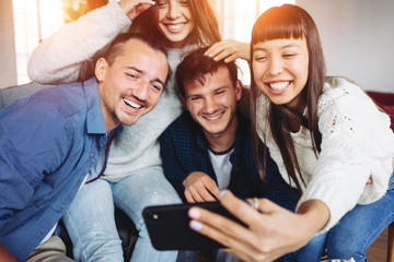 Funny asian woman taking selfie photo with group of her friends together at home party
