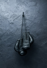Wall Mural - old boxing gloves hang on nail on textured wall