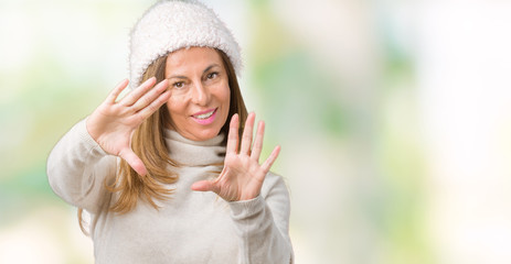 Beautiful middle age woman wearing winter sweater and hat over isolated background Smiling doing frame using hands palms and fingers, camera perspective