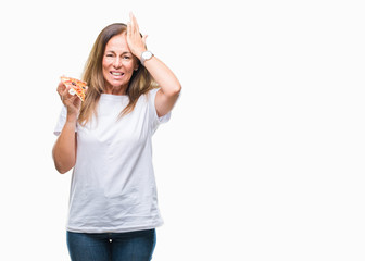 Middle age hispanic woman eating pizza slice over isolated background stressed with hand on head, shocked with shame and surprise face, angry and frustrated. Fear and upset for mistake.