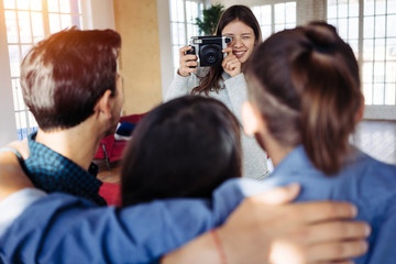 Woman taking photo of her friends using digital camera at home party