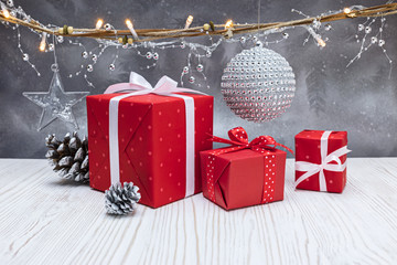 christmas tree decorations, red gift boxes, decorative silver ball and lightning garland on grey frosty winter background
