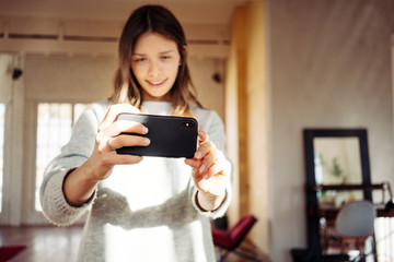 Portrait of handsome woman taking photo using mobile phone camera