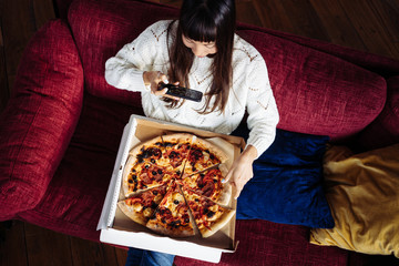 Asian woman eating pizza at home and taking photo of her food to share memory. Top view