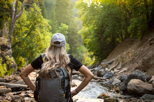 View from behind of a Woman hiking near a mountain stream while on vacation.Close up candid photo of an active female enjoying the outdoors with a beautiful scenic setting