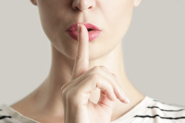 Finger on lips - silent gesture, Woman holding her finger to her lips in a gesture for silence.