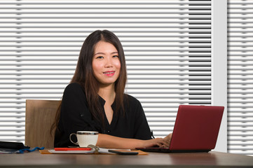 young beautiful and successful Asian Chinese business woman working confident at modern office computer desk in female businesswoman success
