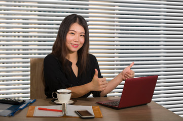 young beautiful and successful Asian Chinese business woman working confident at modern office computer desk in female businesswoman success giving thumb up
