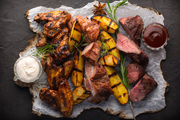 Photo sur Aluminium Viande Assorted grilled meat and potatoes on black background