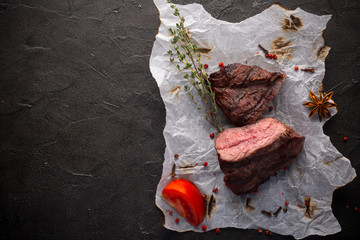 Grilled ostrich steak with spices on black