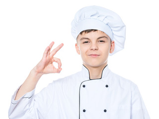 Handsome teen boy wearing chef uniform making ok gesture. Portrait of a happy cute male child cook, isolated on white background. Food and cooking concept.