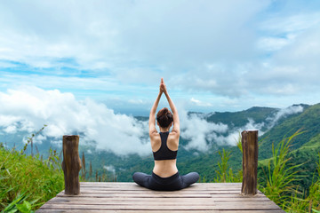 Healthy woman lifestyle balanced practicing meditate and zen energy yoga on the bridge in morning the mountain nature. Healthy life Concept.