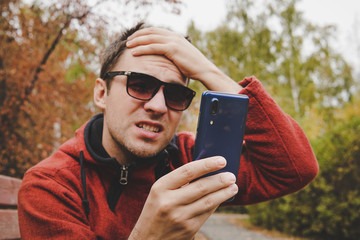 young guy reads news or SMS on a mobile phone and holds his head with his hand. disappointment of the message on the phone. Problems in online communication. disappointing, frustrate