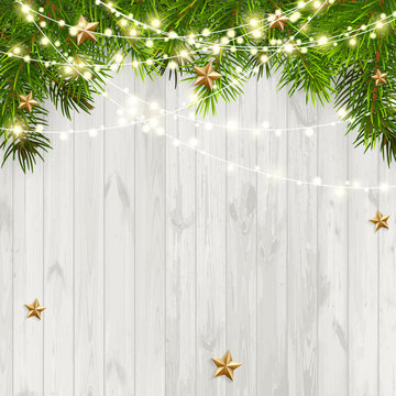 Christmas background with green branches and garland on old white wooden background.