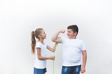 healthy slim girl tease big fat boy measuring his muscle with tape copyspace