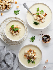 cauliflower potato soup puree on white marble tabletop, Creamy cauliflower soup with toasted bread croutons. Vegetarian healthy food concept. Ideas and recipes for winter meal. Top view or flat lay