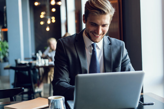 Attractive businessman using a laptop and smiling while working in cafe