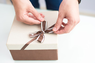Closeup of man wrapping gift. Person tying bow on gift box. Gift concept. Cropped view.