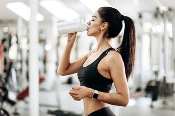 Slender girl  dressed in black sport clothes is drinking water from the bottle in the gym